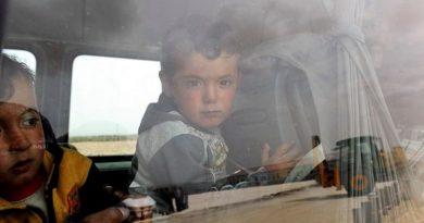 criança síria olha pela janela do autocarro
