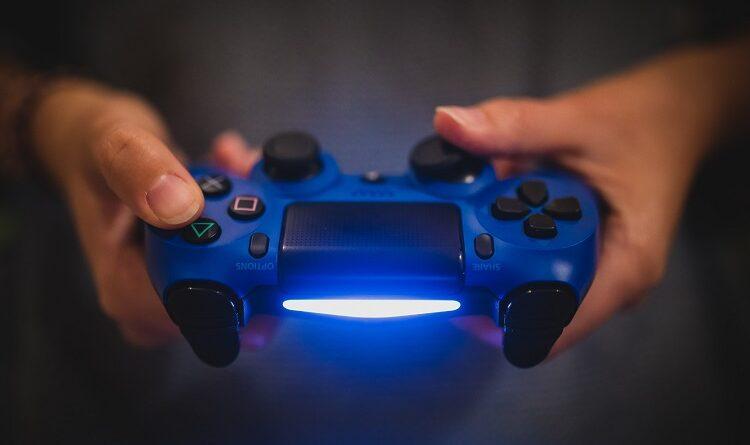 Imagem de uma consola com as duas mãos de um jogador